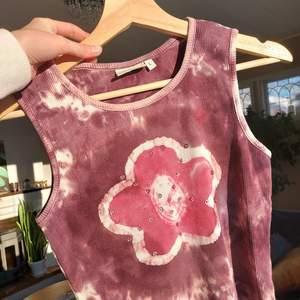 Ett batikfärgat linne med en rosa blomma🌸🌸 blomman har även små paljetter på sig vilket är fint och den passar verkligen in i early 2000's viben! Står L men passar definitivt mindre också (jag är S)