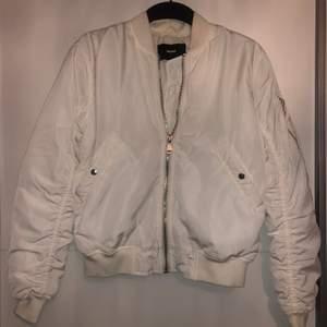 En vit bomber jacka med silverdetaljer. Köpt från bikbok, använd 2-3 gånger.
