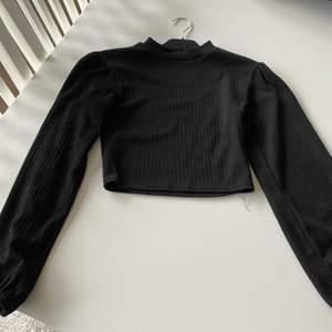 En svart tröja som är lite croppad. Hög hals. Fint mönster. Lite puffiga armar, inte för mycket. Lite ihop draget på axlarna vilket gör tröjan väldigt fin och gullig på än, ser nästan ut som lite axelvadd fast det inte är det.