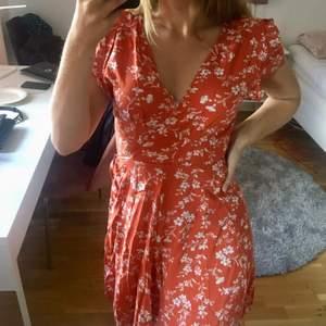 HELT NY med lappen kvar! Jättegullig röd/orange blommig omlottklänning i storlek S från Zaful. Det är en knytning i sidan så man kan justera den hur man vill!🧡Tyvärr kommer den aldrig komma till användning hos mig och säljer den därför vidare:)