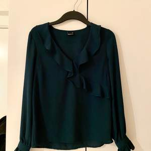 Säljer en mörkgrön blus med volanger på från Gina Tricot. Färgen är orättvis på bilden då den är lite ljusare mörkgrön i verkligheten. Den är i storlek 36. Säljer den för 120kr plus frakten💚