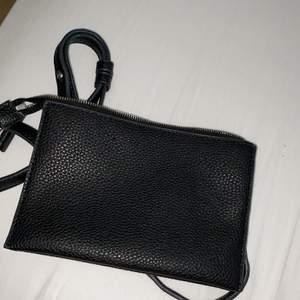 En liten svart väska med olika fack i fint skick. Använd ett fåtal gånger.