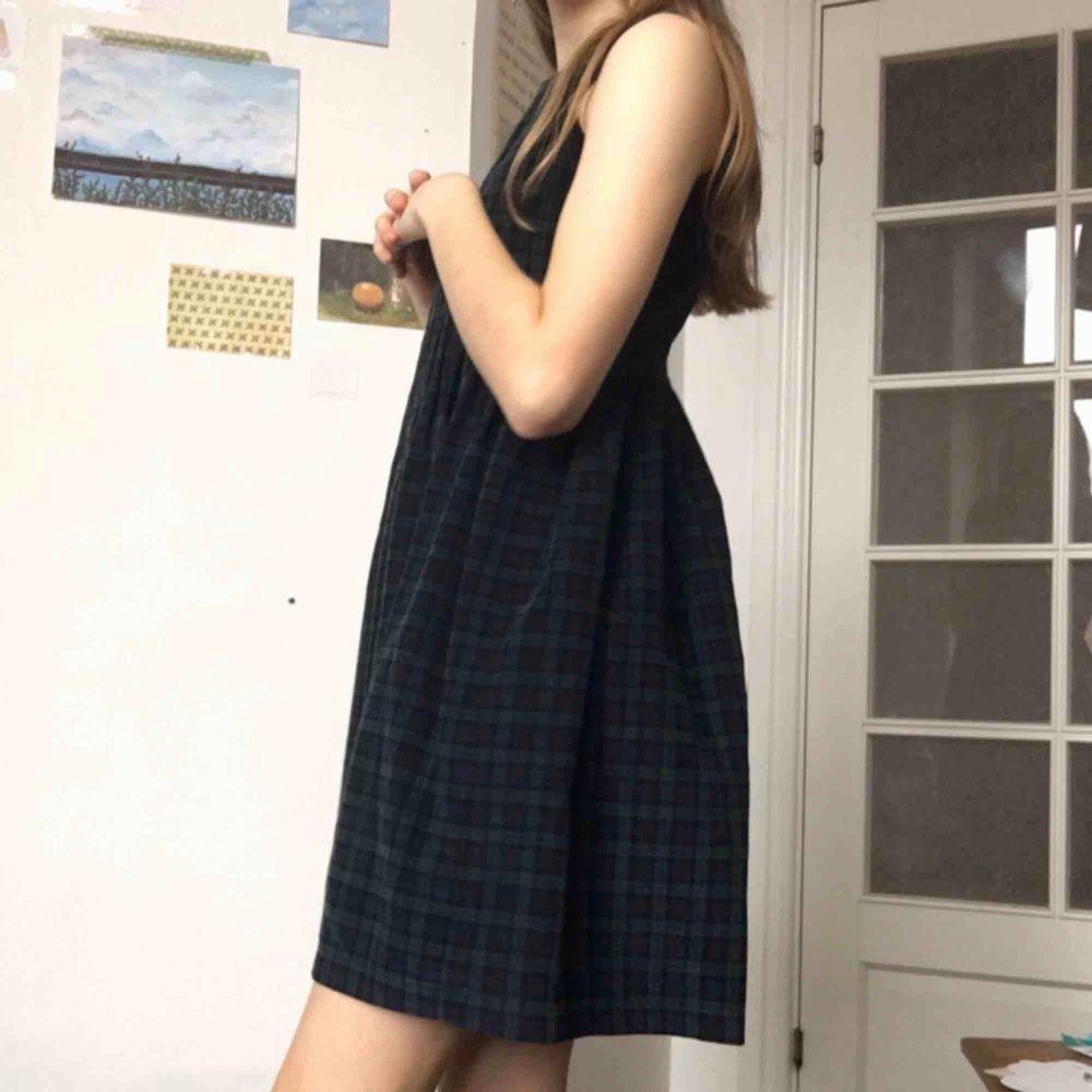 En mörk rutig klänning som passar perfekt till både vinter och sommar. Manchesterliknande tyg. Mönster i svart, marinblå och mörkt grönt. Dragkedja där bak. Hög midja. Bara använd några få gånger. Går till lite över knäna på mig som är 1,67 :). Klänningar.