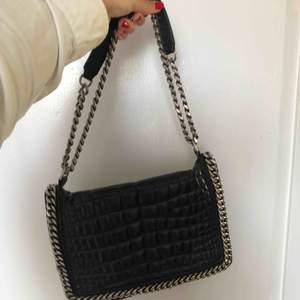 Skinnväska från Zara med kedja. Använd så finns slitage vid knappen. Nypris runt 1200 kr.