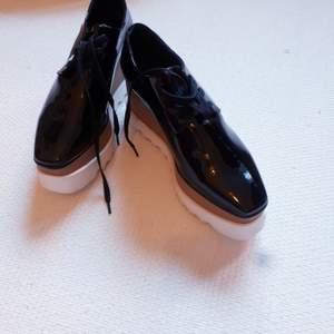 Supersnygga skor från Jessica Buurman i svart lack och träimitation. Endast använda ett par ggr så i nyskick. Nypris ca 1300 kr. Köpare står för frakt, men jag kan mötas upp i Stockholm.