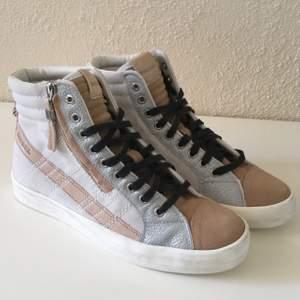 Höga diesel-sneakers med färger av  beige, silver, vitt och svart. De har även en dragkedja på yttre sidan av skon.             Aldrig använda 🖤 👟