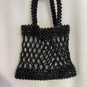 Väska gjort av pärlor, ena fästet vid handtaget är lite löst