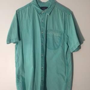 Grönblå kortärmad skjorta, tvättad färg, hel och ren.