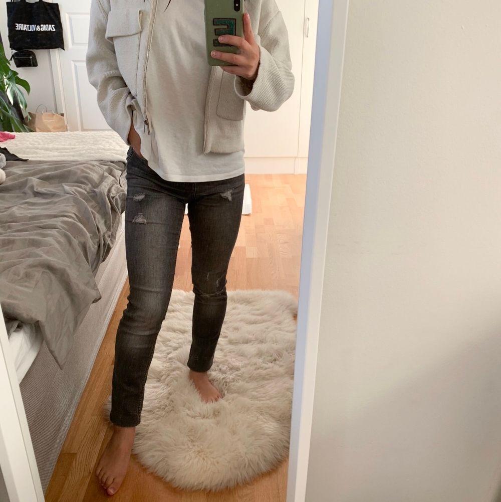 Assnygg jeans från hm i grå sliten färg med några slitningar. Rå kant längst ner men pga att de är för långa har de vikts upp. Jättebra skick 💕💕💕☺️🥺 w 25 som en xs . Jeans & Byxor.