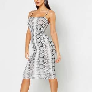 Lång klänning med grått ormmönster. Använd under en semester, väldigt skönt och mjukt material.