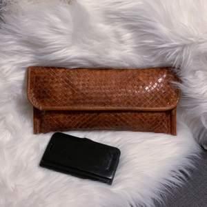 Liten smidig väska i vävt läder. Handgjord i Portugal, där jag köpte den. Sparsamt använd. Litet fack inuti. Äkta läder. Mått: 32x15cm (mitt klumpiga mobilfordral är med som storleksguide)