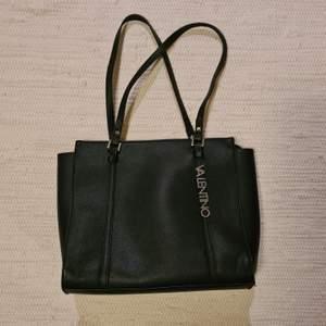 En svart Valentino handväska som har måttet 40x30cm. Nypris: 1250 kr. Den är lite sliten på något hörn, därav lågt pris. Det syns endast om man kollar noggrant. Frakt tillkommer. Betalning sker via swish:)
