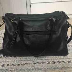 En svart even&odd väska som är knappt använd, original pris 350kr.Skinn imiterat material, två korta handtag och ett reglerbart långt band. Väskan har  två små fack med dragkedja och två mindre öppna.