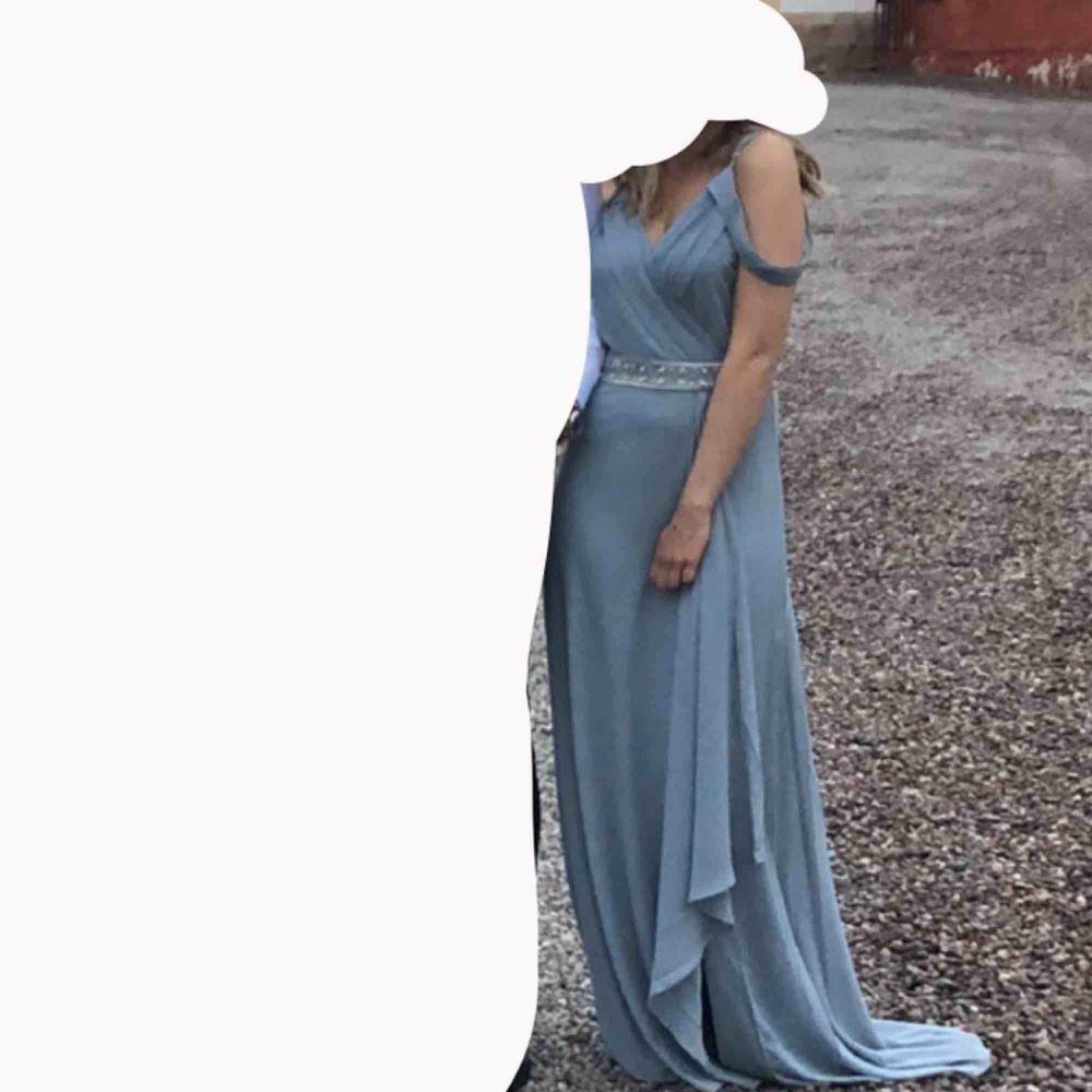 INTRESSEKOLL Superfin balklänning som jag inte tyvärr inte kommer få användning av igen.  Grå/blå färg med glitterbälte och slits. Lite lång på mig som är 166cm men är lätt att sy upp om man inte vill ha lite släp.  . Klänningar.