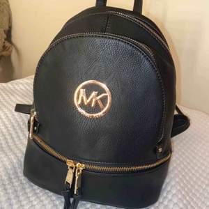 AAA-kopia Michael Kors ryggsäck. En liten gullig super snygg och classy ryggsäck. Svart imitationsläder med guld detaljer. Säljes pågrund av att den inte kommer till användning. Nästan aldrig använd, som nyskick 🥰