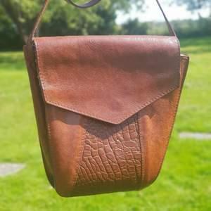 Vintage väska i kvalitetsläder. 🌻🦋 I bra begagnat vintage skick. Crossbody. Får plats med mobil, plånbok och allt man behöver för en utekväll. En ficka med dragkedja,och en utan. Först till kvarn! 💫+frakt 66kr