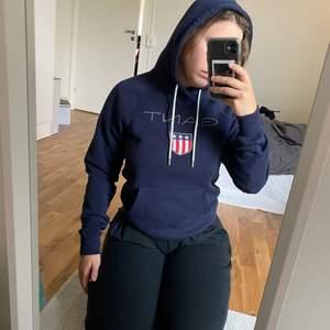 Marinblå Gant hoodie i jättebra skick. Storlek xsmall men det är en herrmodell så den sitter som en small. Säljer eftersom den har blivit för liten. Inga defekter. Frakt tillkommer