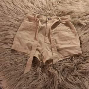 Ett par beige shorts med knytning från bik bok Storlek 38