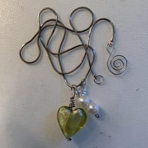 Silverkedja med ett grönt glashjärta, en liten vit blomma och två vita pärlor💚✨