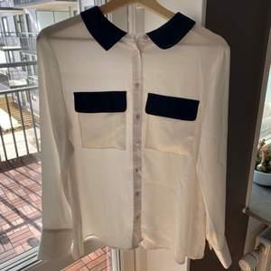 Skjorta i lite halvglansigt tyg i vitt med mörkblå detaljer. Fint skick inga anmärkningar. Passar även S.