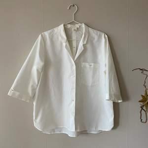 En grädd vit kortärmad skjorta i storlek 42, den är V ringad och öppen i halsen med svarta små detaljer. Tröjan är ganska transparant
