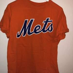 Orange T-Shirt med blått Mets tryck över bröstet. Uppvikta ärmar, den perfekta orangea färgen🧡🔥