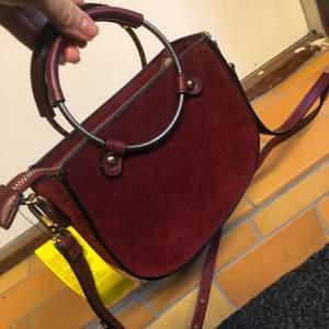 Oanvänd vinröd väska i mockaimitation med lapp kvar. Snygga handtag med gulddetaljer. Kan användas både som axelremsväska eller handväska.