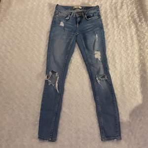 Tighta jeans med hål från Gina tricot i storlek W.24, modell Kristen 💜💜 Lågmidjade. Jeansen är i mycket fint skick och är använda enstaka gånger, säljer då jag inte kan ha dessa längre. Samfraktar gärna med andra plagg och betalning sker via Swish <33