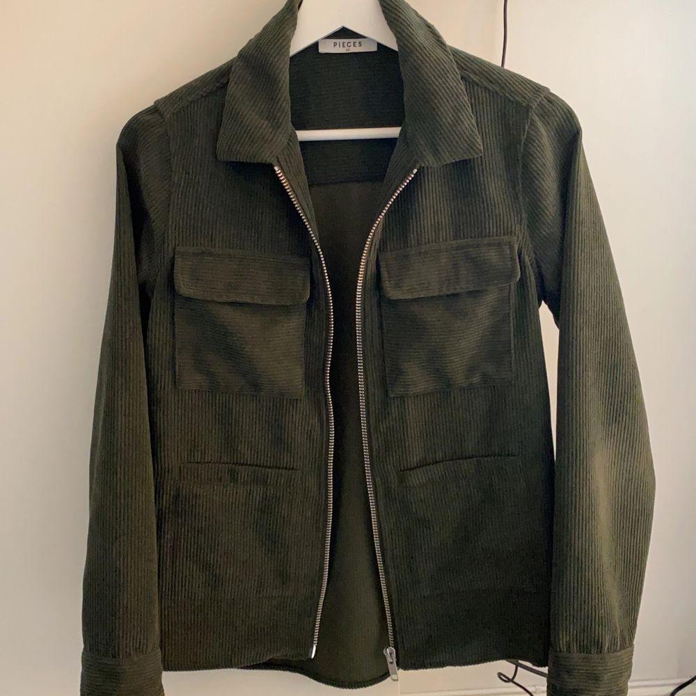 Miltärgrön overskirt i Manchestertyg storlek XS från märket Pieces. Använd fåtal gånger och i super skick! Bud accepteras i kommentarerna:) köpare står för frakt.. Skjortor.
