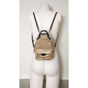 Liten ryggsäck i guldfärgad mjuk läder, djurmönstrad. 2 in 1: ryggsäck och crossbody! Den har en liten ficka på insidan också. Mått: 20x15x10 cm