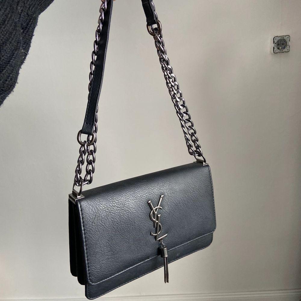 Superfin svart väska med YSL logga på (ej äkta). Sparsamt använd, justerbara band, gott med utrymme! Skriv vid frågor, frakt tillkommer.💕. Accessoarer.