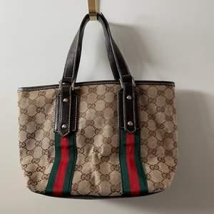 En liten Gucci handväska köpt secondhand, lite sliten vid handtaget sedan innan. Annars i bra skick använd få gånger. (ej äkta)