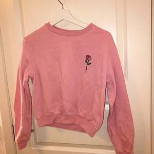 Rosa sweatshirt med en ros på, superfin färg och knappt använd. Är i storlek XS men passar även en S. 50kr plus frakt eller bud!!