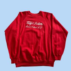 Röd sweatshirt med tryck strl L. 66 kr spårbar frakt. Notera litet igensytt hål på framsidan av tröjan.  Skicka meddelande vid frågor/fler bilder! Notera att små defekter kan finnas då den inte är ny. Större brister nämns tydligt i annonsen/visas på bild. OBS! Bud är bindande!!!!!!!