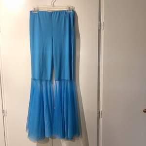 """Ett par ljusblå byxor med ett """"flowy"""" material på botten. Är lite 70-tals aktigt. Storlek XS-S skulle jag säga. Är använda en gång. Köparen står för frakten"""