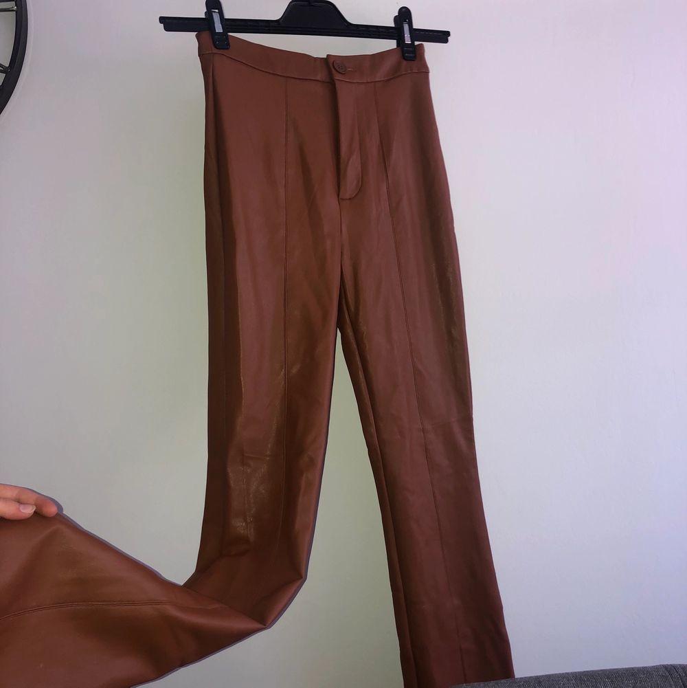 Bruna utsvängda skinnbyxor från NAKD. Storlek 32 men passar en storlek 34 lika bra!! Köpare står för frakten.. Jeans & Byxor.
