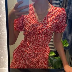 En röd blommig klänning i fint skick. Använd max 2ggr men säljer där av att jag inte passar i färgen röd. Den har puff armar, v-ringad, en volang och ett midjeband man kan knyta hur man vill runt midjan så passar väldigt bra. Fin passform💖storlek 34/XS men passar som en S. Köpte för 300 men säljer för 100kr +  30krfrakt.