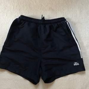 Ett par Lonsdale shorts i strl S, Navy. Använda ett flertalet gånger men i gott skick samt felfria. De har dragkedjor. Nypris: 15 Brittiska pund.