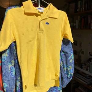 Gul och blå äkta vintage pikétröja från chemise lacoste, bra skick. OBS inga fläckar, det som syns på bilden är en skugga från mitt fönster haha.