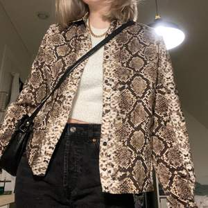 Brun & beige skjorta med ormskinnsmönster från NA-KD i storlek 38. Använd fåtal gånger därav fint skick