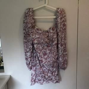 Så fin klänning från Nelly.com! Perfekt klänning till sommaren med blommor i vitt och rosa. Storlek 40, men känns mer som en 38. Aldrig använd.