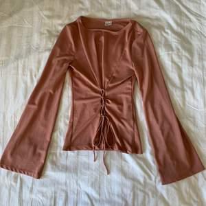 Säljer denna superfina ljusrosa blusen!💗 Blusen är i bra skick. Den har en fin design med snörning i midjan och vida ärmar. Storlek S. Köparen står för frakt.