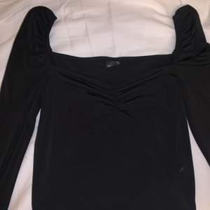 En söt svart långärmad topp från Gina tricot. Använd en gång, tyvärr för liten för mig. Passar storlek S-M. Har som en resår framför bröstet.