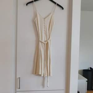 En beige klänning från Mango i storlek S. Detaljknappar fram och knytning i midjan. Fraktkostnaden tillkommer.