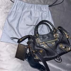 En svart Balenziaga väska med guld detaljer. I bra skick och har alla äkthetsbevis men inget kvitto.