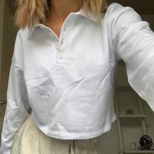Vit (kan se lite ljusblå ut i vissa ljus) tröja med krage i storlek xs. Lite croppad och har långa armar, köpare står för frakt!