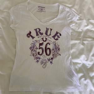 T-shirt från trendiga Y2K-märket True Religion med strasstenar på bröstet. Strl M men sitter mer som S. Möts upp eller så står köparen för frakt med PostNord för 66kr. Vid flera intresserade sker budgivning