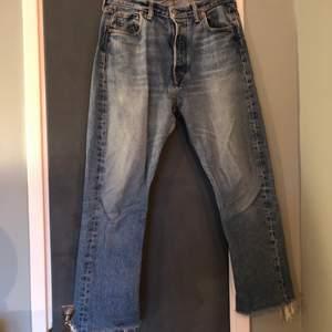 Blå Levi's 501, avklippta redan vid köp i butik, lagade i grenen