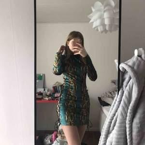 klänning från prettylittlething, aldrig använd bara provad, slits på båda sidorna med snören, nacken är som en turtleneck och klänningen har en dragkedja på baksidan