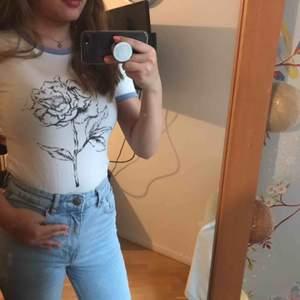 En jättefin och bekväm T-shirt från H&M. Den har en jättefin ros mitt på och helt vit där bak. De blåa ränderna på ärmarna och halsen gör tröja så fin! Den är knappt använd och säljs för att den inte kommer till användning.